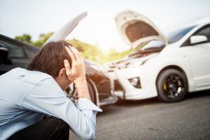 man holding his head watching car accidents